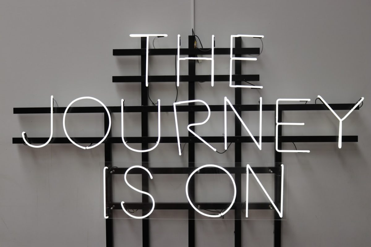 neon lights stating the journey is on