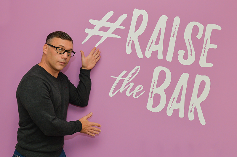 simon Hudson in front of a wall with raise the bar