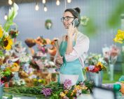 Florist Talking by Smartphone in Shop